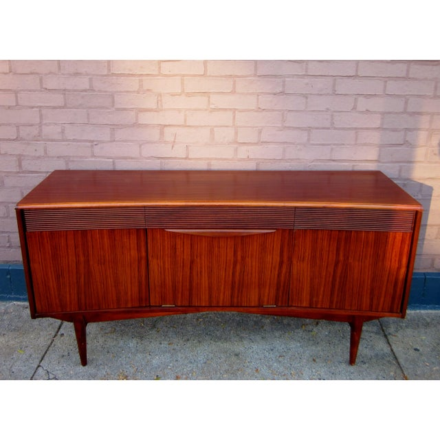This is an absolutely stunning, warm, and sleek vintage Danish modern rosewood and ribbon mahogany credenza or sideboard....