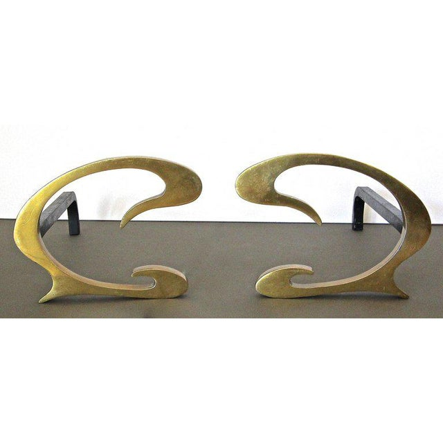 Pair of French Deco solid brass C-scroll shaped andirons. Heavy thick construction. Nice patina to brass.