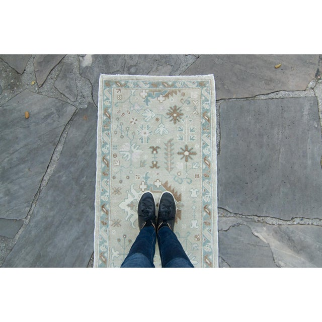 This invitingly vintage Anatolian runner features a schema of inter-linking floral and abstract medallions in muted color...