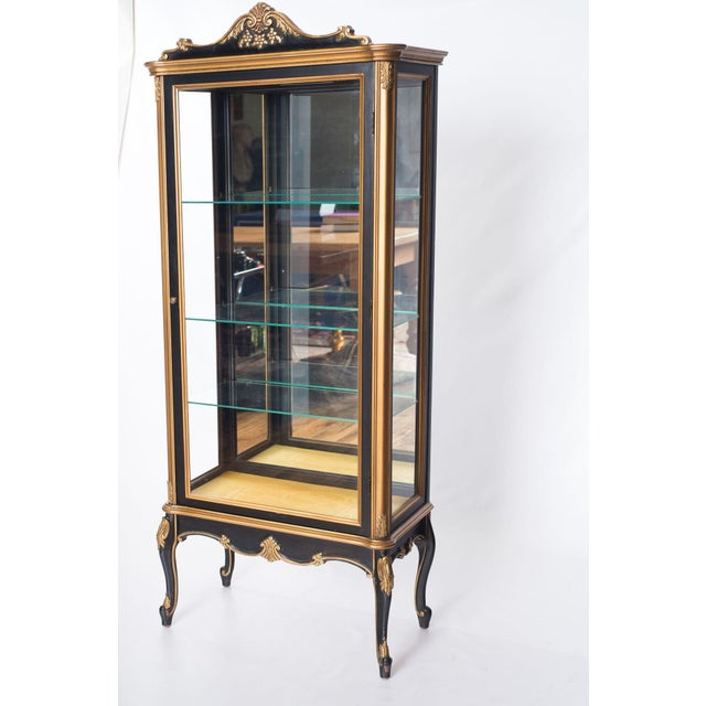 A 1980s French style cabinet featuring a rich gloss black finish and carved gold accents. Three glass display shelves are...