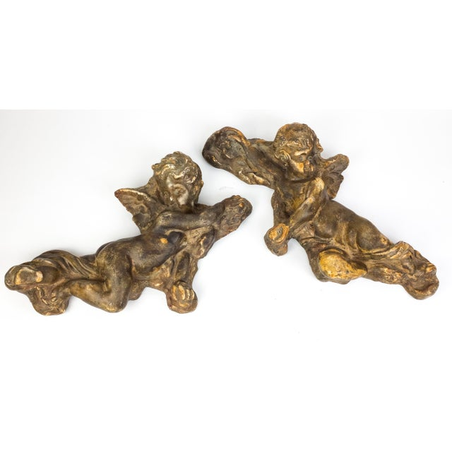 Vintage wall plaques depicting a pair of charming cherubs. Composition material has a nice patina giving them the...