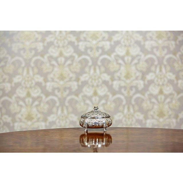 A sugar bowl entirely made of silver with a gilded inside. This item is in a decorative, Neo-Rococo form, which is...