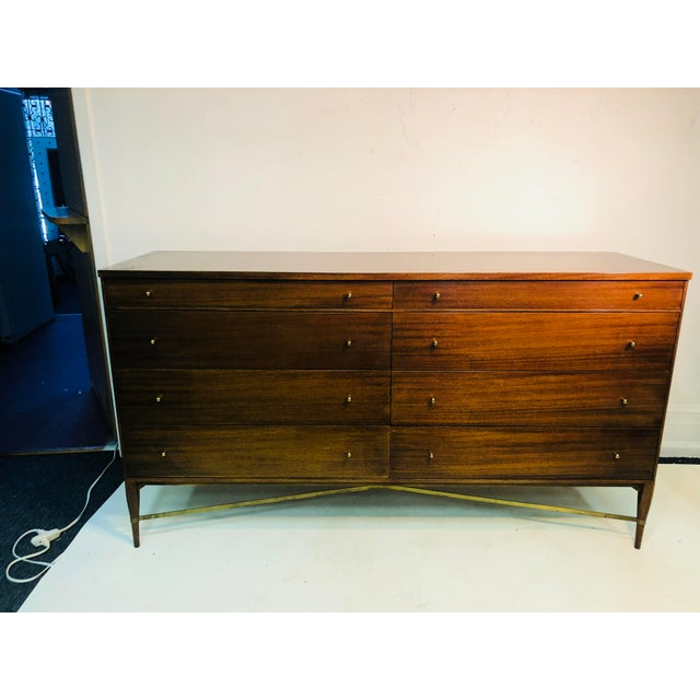 Beautiful deep wood dresser with great modernist brass drawer pulls and stunning brass X design stretcher on the base....