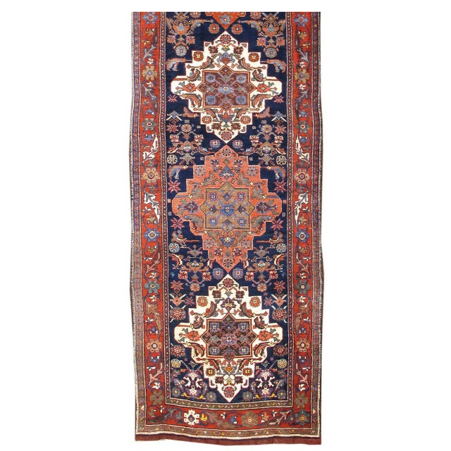 This elegant Bidjar runner draws a column of alternating traditional Persian medallions in red and white against a deep...