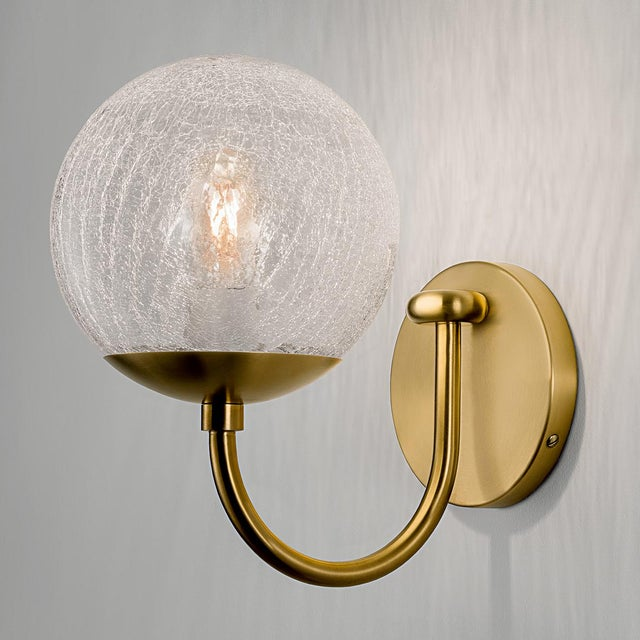 A brushed brass wall light with a single arm with a crackle glass globe. The glass has an integral threaded metal fixing...