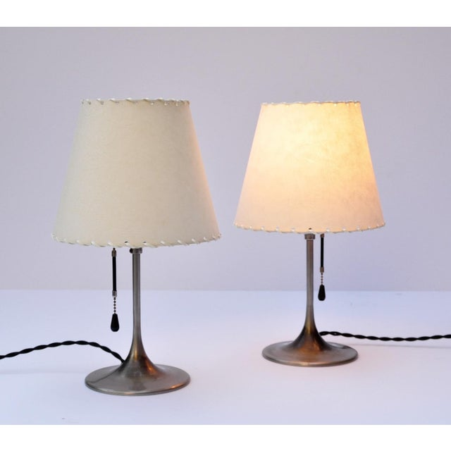 Priced for the pair. Graceful pair of trumpet form bedside lamps in well age nickel plated brass. Both lamps come with...