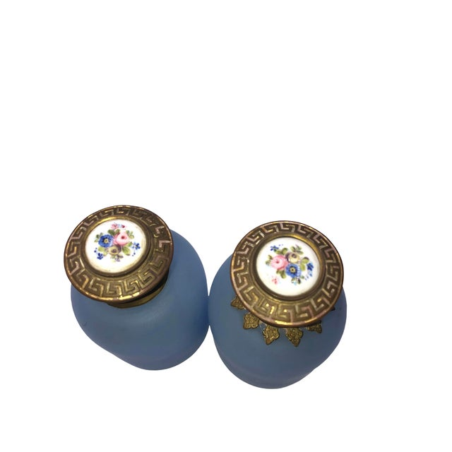 A pair of 19th century french opaline blue perfume bottles with hand painted floral tops.