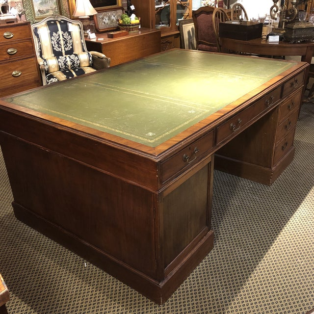 Dating to about 1900, this George III style mahogany double sided partners desk has a rectangular top with an inset green...