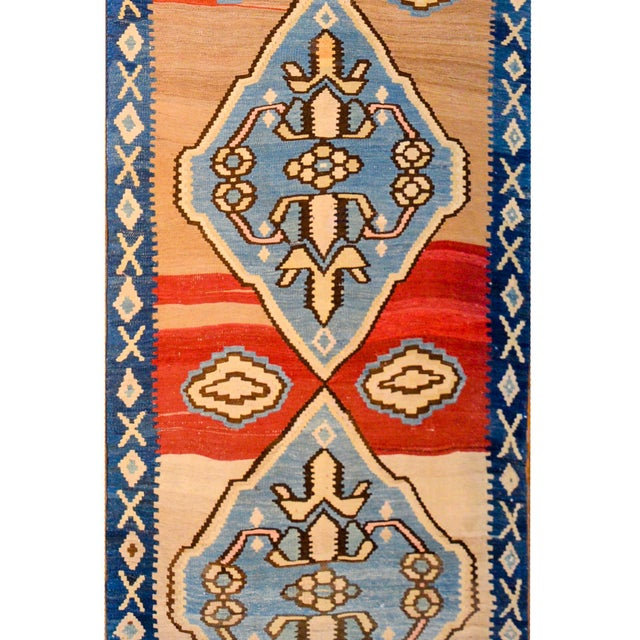 A bold early 20th century Azerbaijani Azari KIlim runner of considerable length with four large indigo diamond medallions...