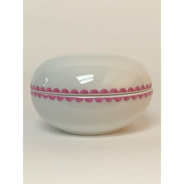 Small round trinket box in white, decorated with a pink scalloped trim from famous Italian porcelain manufacturer Richard...