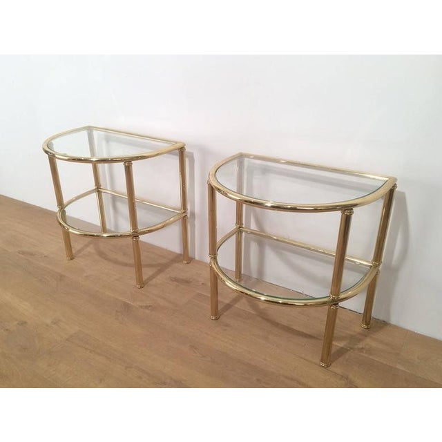 Pair of rounded brass side tables with two rounded feet on the back and on the bottom and two clear glass shelves, French,...