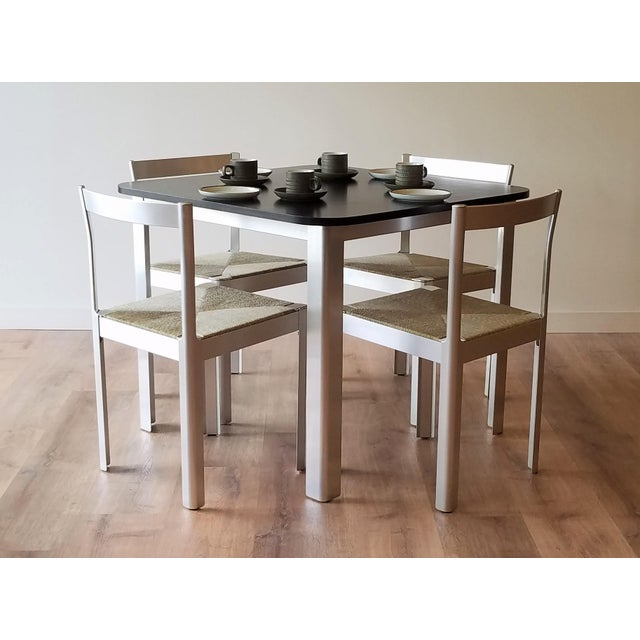 This compact square dining set was made in Italy and brought to American by Hank Loewenstein. The table base and chairs...
