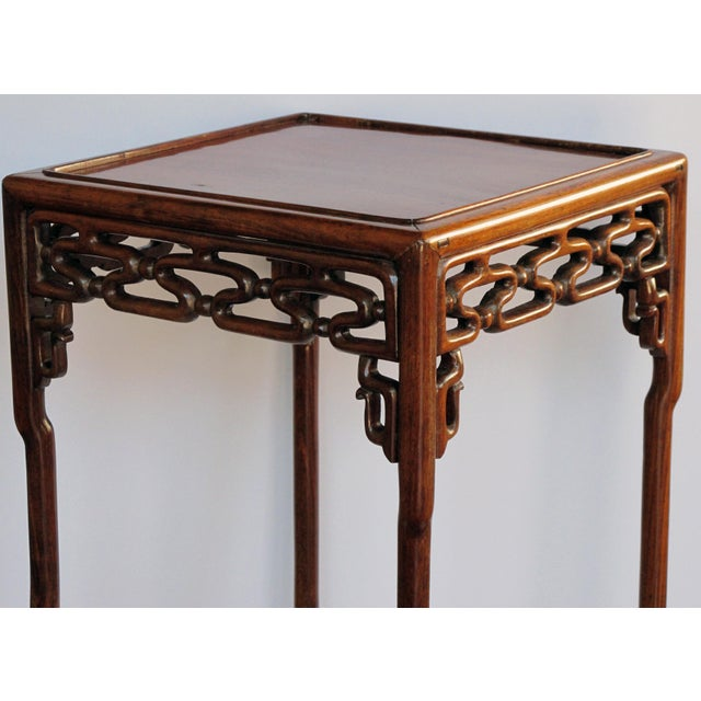 the well-figured square top with recessed center panel within a mitered frame; raised on slender turned supports joined by...