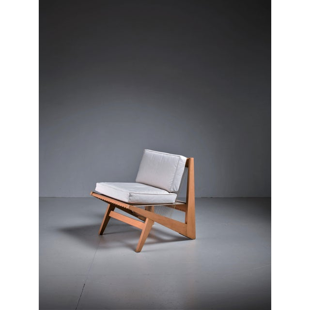 A low lounge chair in the manner of Albert Frey, made of a wooden frame with a woven rope seating. The frame and the...