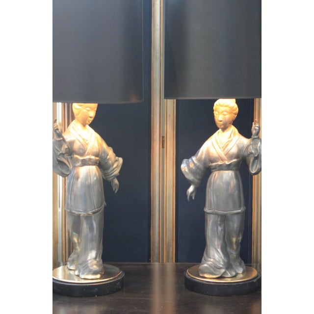 A pair of beautiful Asian zinc figurative table lamps with brass bases and finials.