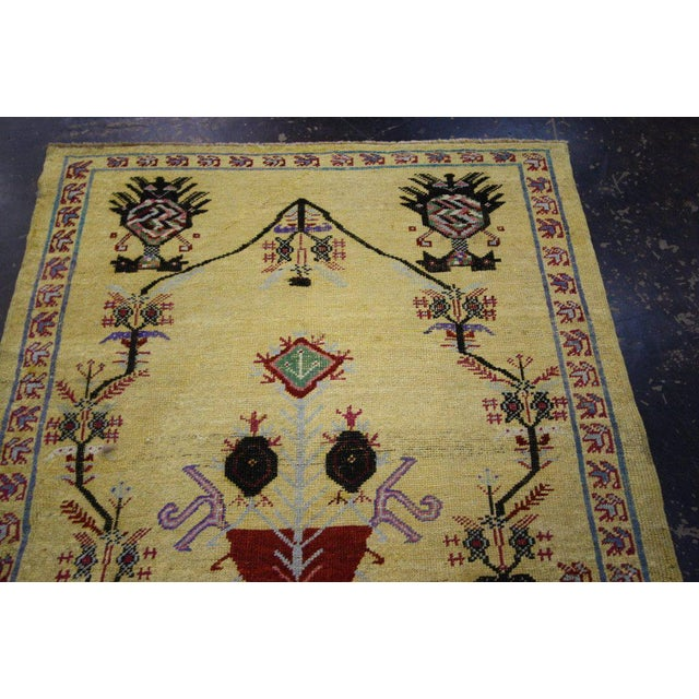 A vibrant, colorful vintage Oushak rug featuring a unique center medallion, vase and tree of life enclosed by radiating...