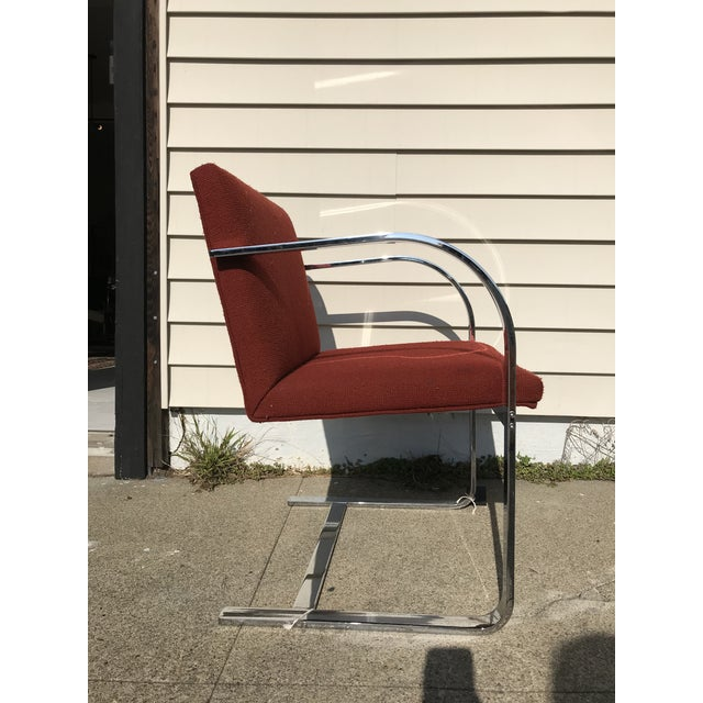 Cantilever chrome arm chair designed by Mies Van Der Rohe for Thonet. Rust colored upholstery. It is in good condition...
