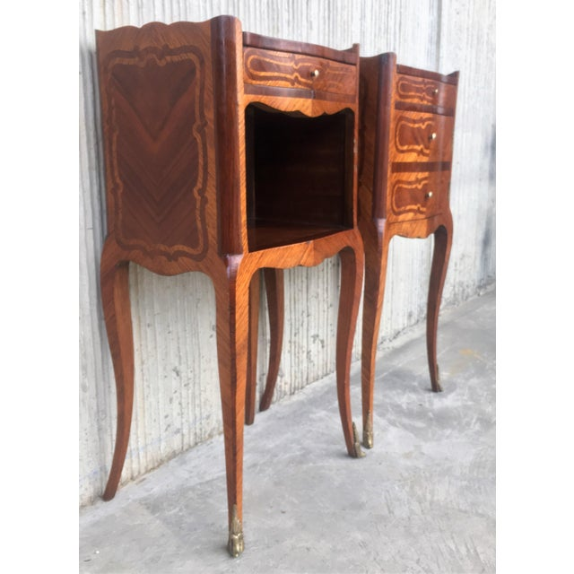 About A pretty pair of French, inlaid kingwood, one drawer nightstands with tray accents, circa 1930. One table has one...