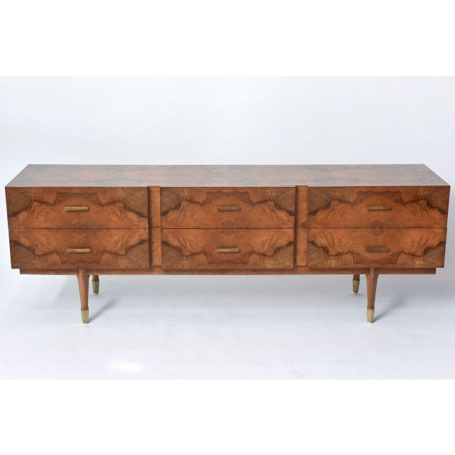All-over in exotic root wood veneers, comprising six drawers over tapering legs terminating in brass caps. This piece...