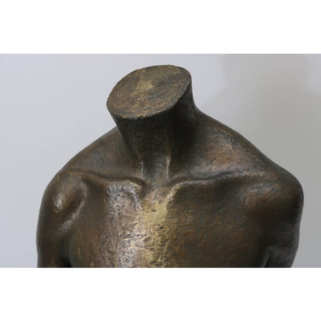 This Mid-Century Modern bronze sculpture of a female torso was created by the American sculptor Lewis Iselin and was...