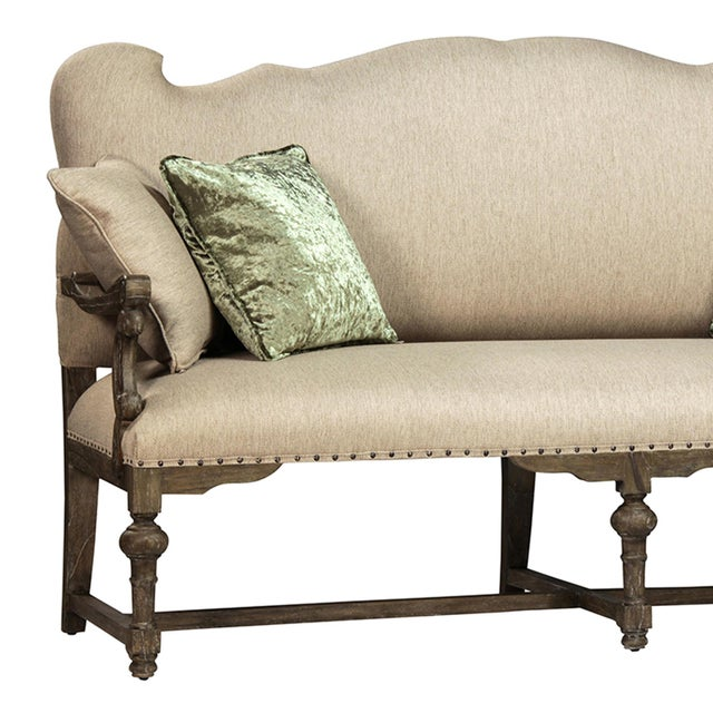Art Nouveau settee upholstered in a beige cotton linen blend. Hardwood Elm frame with antiqued brass nail head details....