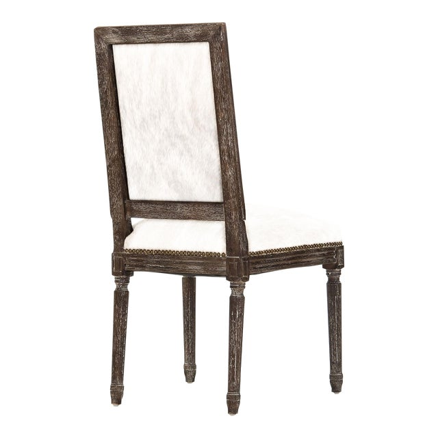 Rectangular back side chair upholstered in white cowhide, on limed grey frame, and filled with foam.