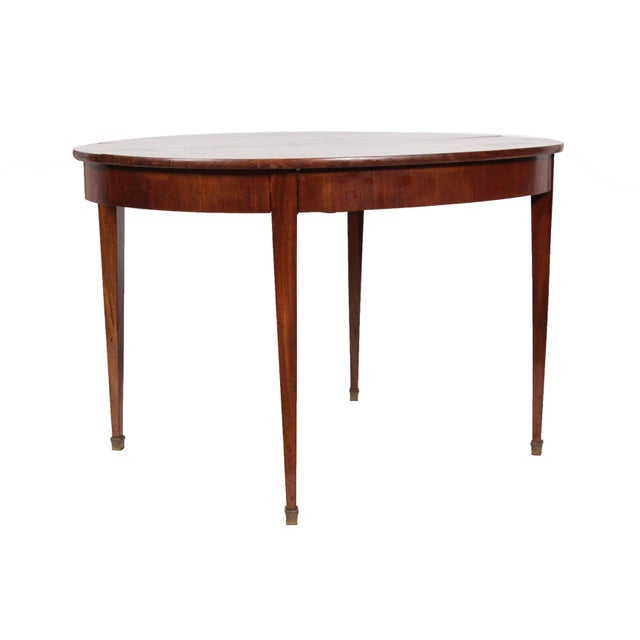 Antique Directoire-Style dining table featuring a time worn mahogany patina top, sabre legs and brass tips on the feet.
