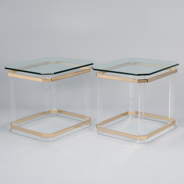 Circa 1970s pair of side or end tables with beveled edge glass tops, clear lucite legs and flat brass plated banding at...