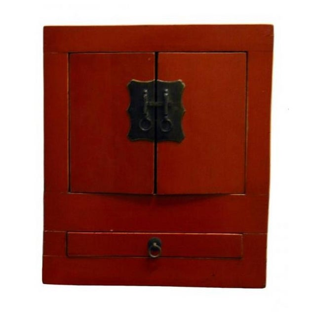 A Chinese cabinet with red lacquer and brass hardware from the 20th century. This elegant but simple red cabinet is...
