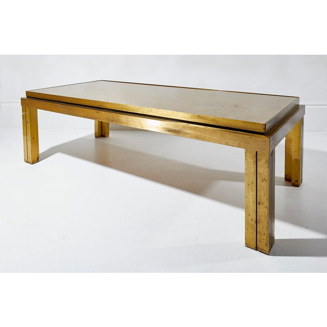 Fine quality lacquered brass coffee table with gold eglomise top attributed to Maison Jansen. Paris circa 1970 Good...