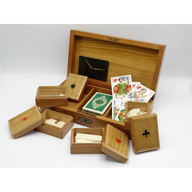 A nice quality antique English games box and contents. This hand crafted oak box features playing card suits on the top...