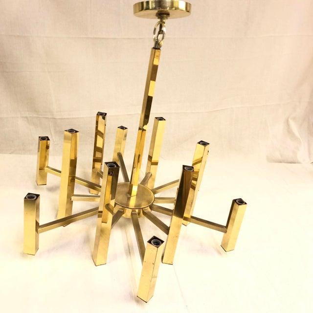 Mid-Century Gaetano Sciolari Polished Brass Twelve Arm Chandelier This vintage geometric candle-style chandelier features...