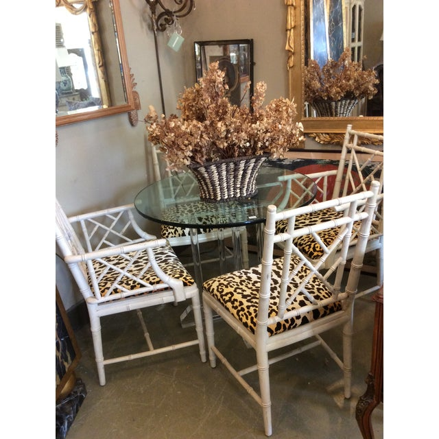 Set of 4 faux Bamboo dining chairs, 2 arm and 2 side, with new upscale leopard upholstery. Distressed off white finish on...