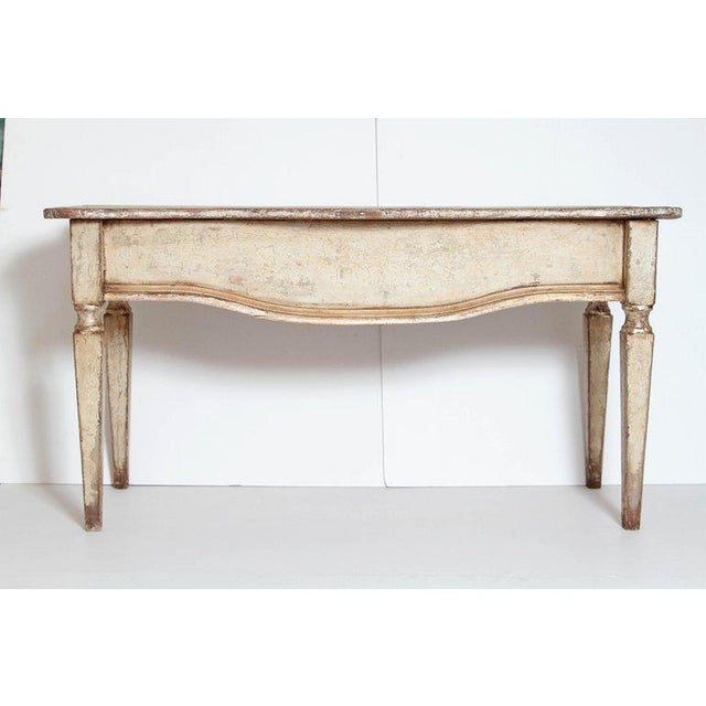 A handsome pair of serpentine shaped top painted and gilt console tables. Molded apron front and square tapered legs. With...