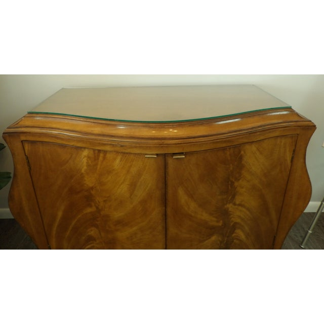 A gorgeous burl wood French Provincial style Bombay cabinet. This piece has exceptional style. This cabinet has a glass...