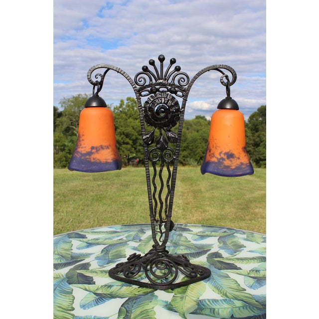 This lamp features a wrought iron base and two lights with thick glass shades. These double lamps are fairly hard to come...