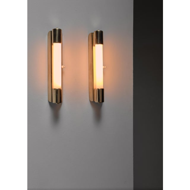 A pair of model 71032 bedside or bathroom wall lights by Mauri Almari for Idman, Finland. The lamps are made of a brass...
