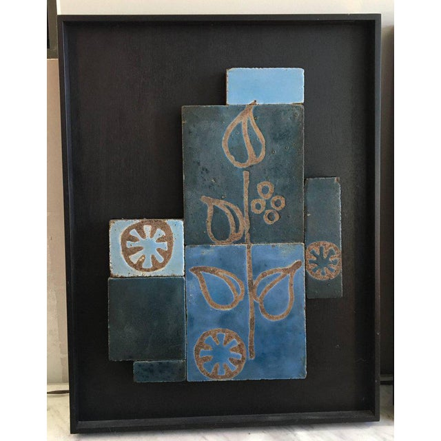 Impressive set of three glazed ceramic tile artworks, all in dreamy blue tones with Primitive floral motifs; substantial...