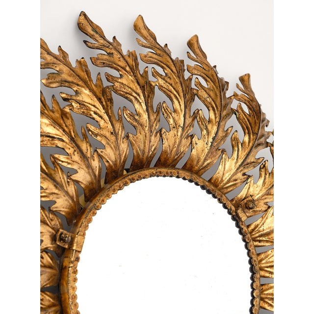 Spanish vintage sunburst mirror with backlight featuring gold leafed embossed tole rays adorning a circular central...