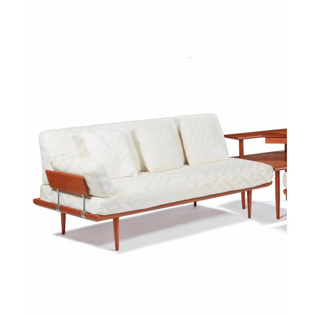 A mid-century modern sectional set comprising three pieces including one love seat, one larger couch, and a central square...