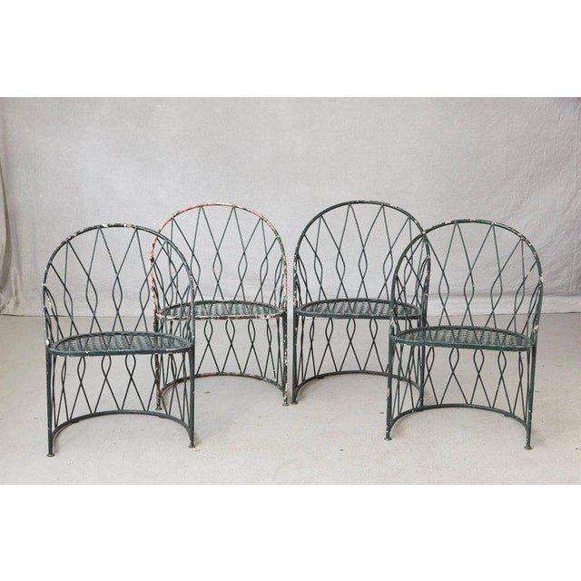 Rare set of four dark green round wrought iron garden or patio chairs by Salterini. The chairs are decorated with a...