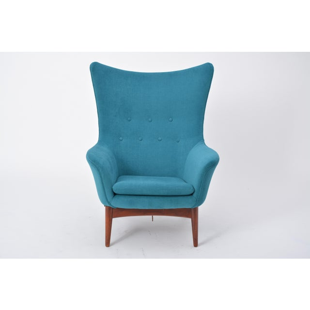 The chair has a rounded design with a subtle wing back and has a reclining mechanism adjusted with a knob on the right-...