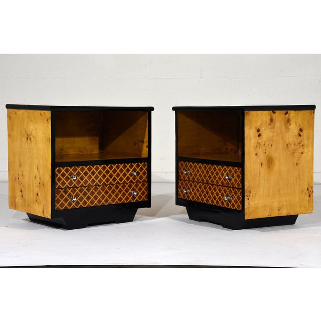 This pair of Mid-Century Modern-style nightstands or side tables is made of wood covered in burl veneers finished in...