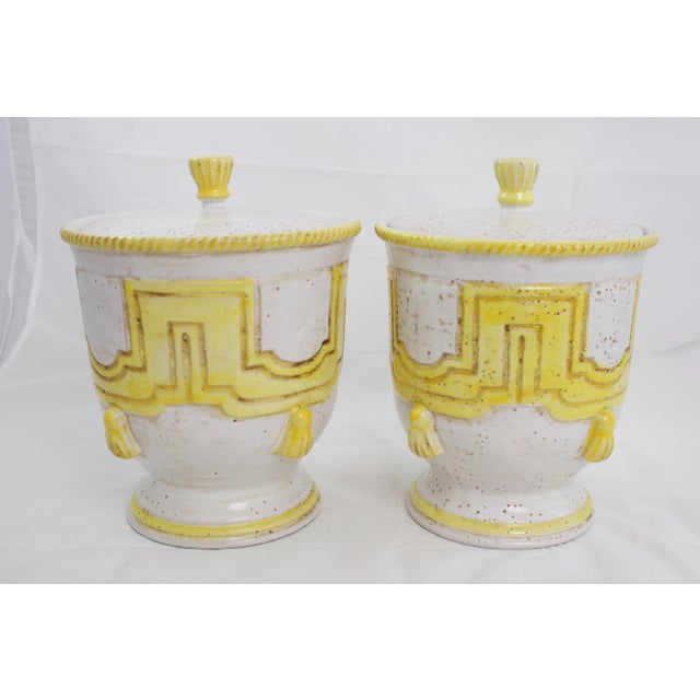 "Pair of mid-century Italian pottery jars with pedestal base and rope and tassel detail. Marked ""Handmade in Italy""."