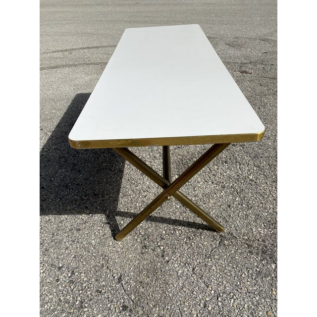 Solid brass coffee table with x-form base white laminated top. Gold edge strip.