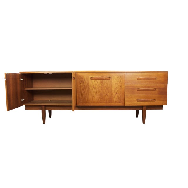 Highly desirable Mid-Century Modern flame teak credenza, English, circa 1960. This authentic, gorgeous credenza is in...