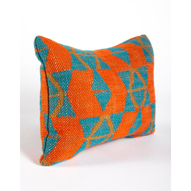 """This small orange and blue geometric patterned pillow measures 12""""x16"""". It would be the perfect travel pillow, or a great..."""