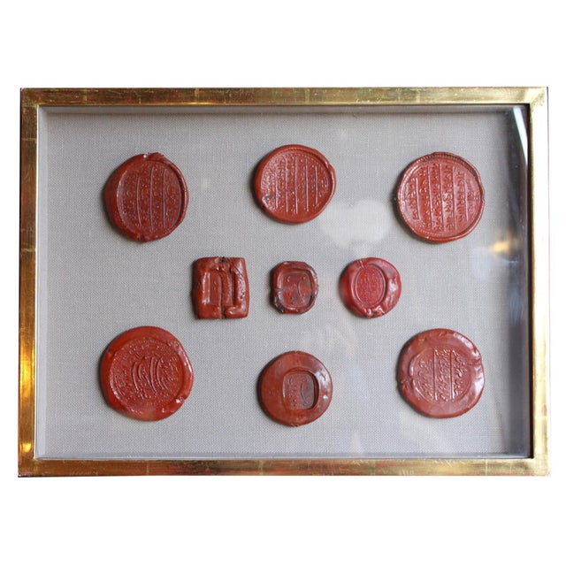 A set of various red intaglio wax seals, framed in a shadow box.