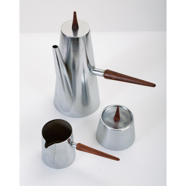 A three-piece coffee service in stainless steel comprising a coffee or teapot, pitcher for cream, and sugar bowl with lid....