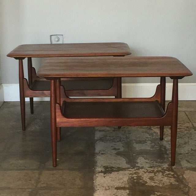Pair of chic two-tier walnut side tables. Beautiful rounded edges and profiled top. Rare in such excellent original...
